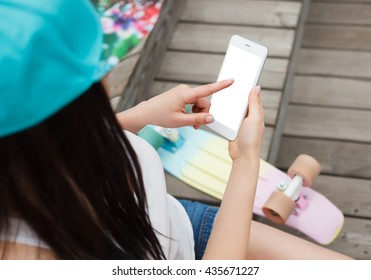 Young girl using her modern phable smartphone with big blank white screen while sitting in the park outdoors with her cruiser skateboard. Big trendy mobile phone, place text on screen