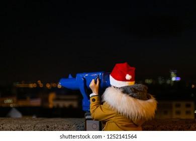 Young girl using pay binoculars at Christmas market, Zagreb, Croatia.