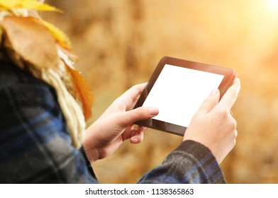 Young girl using small black tablet with white screen in the autumn forest with fallen leaves and sunlight