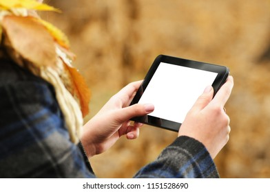 Young girl using small black tablet with white screen in the autumn forest with fallen leaves