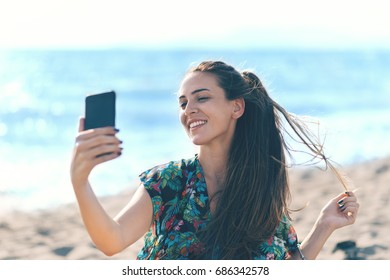 Young girl using smart phone on the beach
