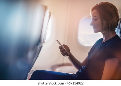 Young girl using smartphone, businesswoman working while flying at plane, Young woman using the internet at airplane, blurred background, shallow DOF.