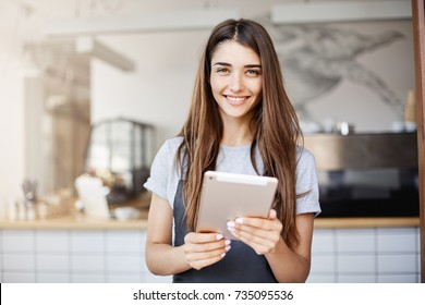 Young girl using a tablet computer running her cafe looking at camera happily smiling waiting for customers.