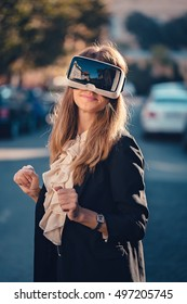 Young girl using virtual reality headset VR glasses on the street and is feeling awesome in augmented reality by morning sunrise light