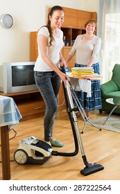 Young girl with vacuum cleaner helps her mother do housework