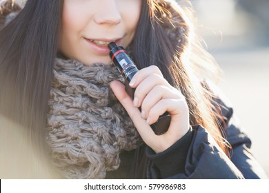 Young girl vaping outside in cold winter day.Smiling brunette girl vapes ecig with ejuice.vaper smokes electronic cigarette outdoor