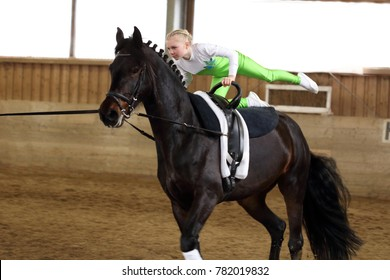 young girl is vaulting on a black horse