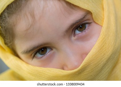 young girl with a veil covering her, close up, studio picture