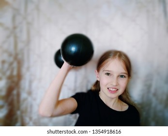 A young girl is very thin decided to go in for sports. She effortlessly lifts very heavy dumbbell.