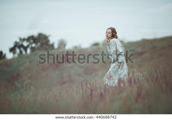 Young girl in vintage dress walking through sage flower field.