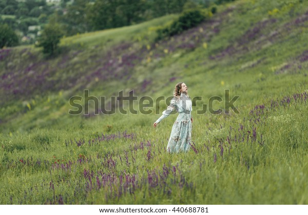 Young girl in vintage dress walking through sage flower field.
