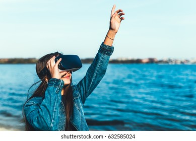 Young girl in virtual reality glasses outdoor