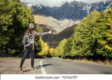 young girl waiting for the car on the background of the mountains (hitch-hiking)