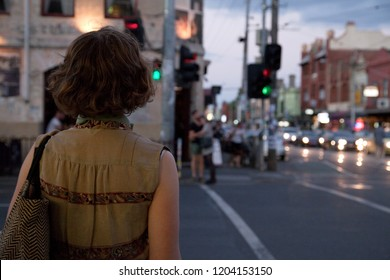 Young girl waiting at twilight to cross a street in Fitzroy melbourne. The image has a gentle, longing romantic mood.