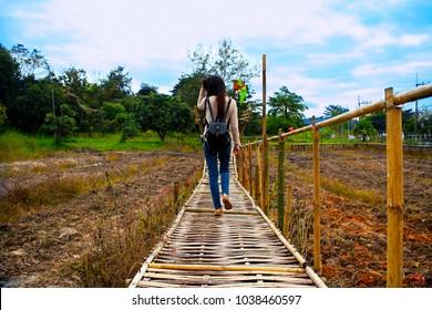 Young girl is walking alone on wood bridge.