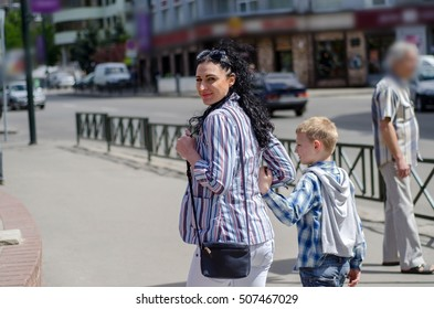 young girl walking in the city with her young son