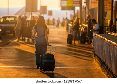 Young girl walking with luggage walking at airport terminal during a wonderful sunrise time, travel concept, journey lifestyle.