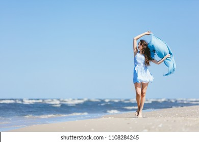 Young girl walking on the beach with blue scarf waving on the wind. Summer leisure activities.