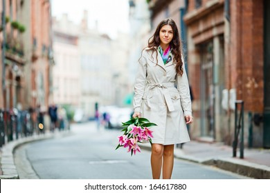 Young girl walking on an old european city street with a bouquet of lilies in her hand