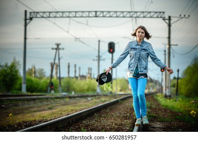 Young girl walking on the railway. Top views