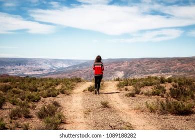 Young girl walking on the road near Laguna Colorada , Uyuni, Bolivia.