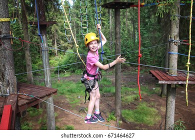 young girl is walking on a rope park
