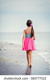 Young girl walking on sandy beach, looking at sea
