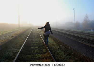 young girl walking on the train tracks