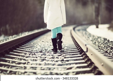 Young girl is walking in the railroad tracks. Image taken during spring time and there is some snow left on the ground. Image has a vintage effect applied.