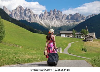 Young girl walking with suitcase on small street to the mountain.freedom traveling in Dolomites,Italy