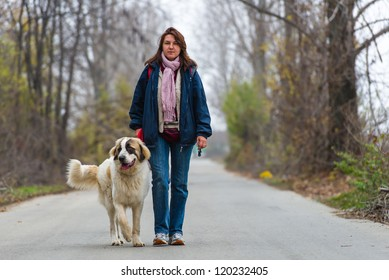Young girl walking and training her Bucovina shepherd dog on a rural empty road