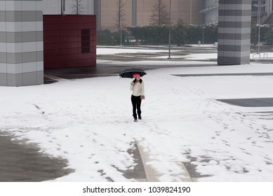 Young girl walking under the snow