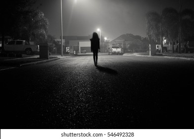 Young girl walking under the street lights