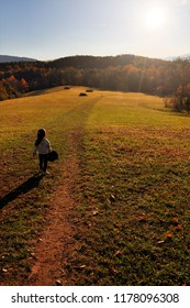 A young girl walks in a beautiful meadow in the Blue Ridge mountains on an autumn day.