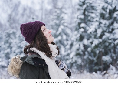 A young girl walks in a beautiful winter forest among tall trees, firs, covered with snow. Magnificent nature and views. Fashionable image, clothes, parka, hat, mittens, blue jeans.