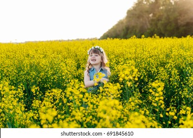 A young girl walks through a flowering yellow field