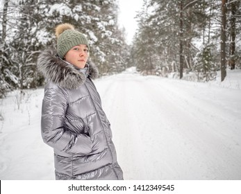 A young girl walks in the winter forest and enjoys silence. She is wearing a hat and a jacket of silver color.