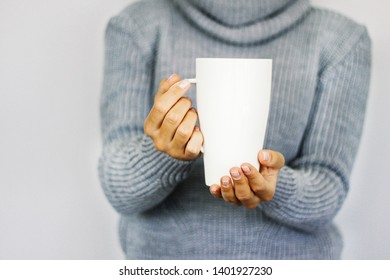 A young girl in a warm gray sweater holding a large white cup. Conceptually for the winter holidays. Winter mood. Coffee mug in female hands. Woman drinking hot coffee