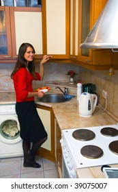 A young girl washes the dishes in the kitchen