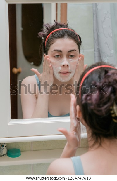 a young girl washes her face in the bathroom with special cosmetics that prevent acne