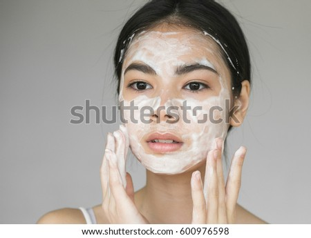 Young girl washing her face with soap.
