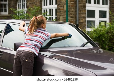 Young girl washing windshield in parking lot, rear view