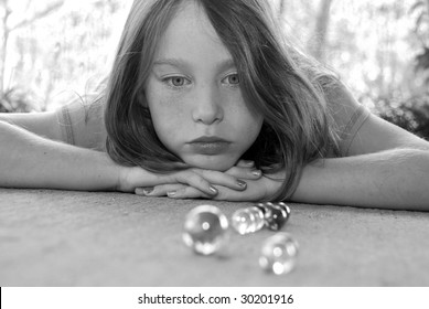 Young girl watching marble game with serious face