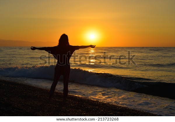 Young girl watching the sunrise on the beach. Concept of serenity