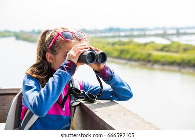 Young girl watching through binoculars from a wooden balcony