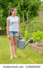 a young girl with a watering can in the garden