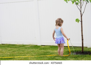 A young girl waters a young tree in her back yard helping it grow