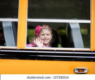 Young girl waving from school bus window
