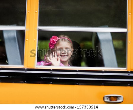 Young girl waving from school bus window