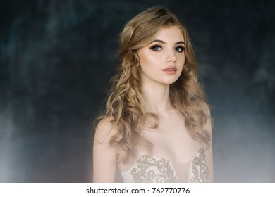 young girl with wavy hair and fashion make up,  in beautiful dress posing in studio